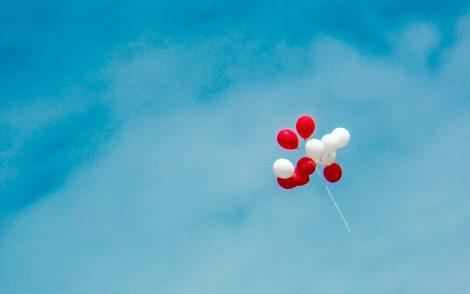 Rote und weisse Ballone, die in der Luft fliegen